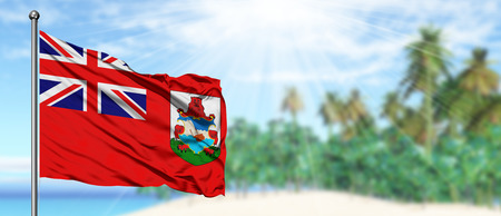 Waving Bermuda flag in the sunny blue sky with summer beach background. Vacation theme, holiday concept.
