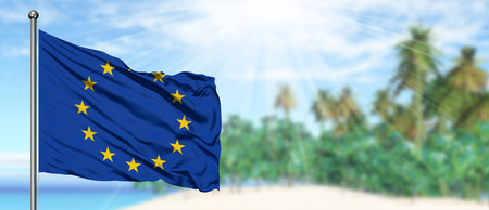 Waving European Union flag in the sunny blue sky with summer beach background. Vacation theme, holiday concept.