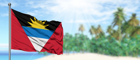 Waving Antigua and Barbuda flag in the sunny blue sky with summer beach background. Vacation theme, holiday concept.