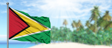 Waving Guyana flag in the sunny blue sky with summer beach background. Vacation theme, holiday concept.