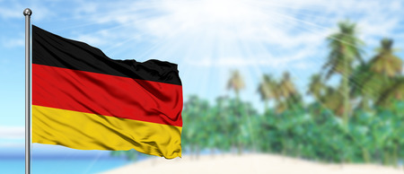 Waving Germany flag in the sunny blue sky with summer beach background. Vacation theme, holiday concept.