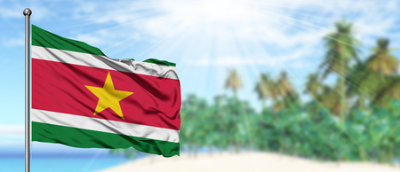 Waving Suriname flag in the sunny blue sky with summer beach background. Vacation theme, holiday concept. Foto de archivo