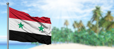 Waving Syria flag in the sunny blue sky with summer beach background. Vacation theme, holiday concept. Imagens