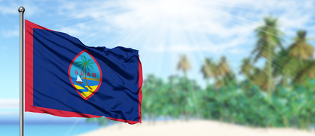 Waving Guam flag in the sunny blue sky with summer beach background. Vacation theme, holiday concept. Standard-Bild