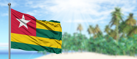 Waving Togo flag in the sunny blue sky with summer beach background. Vacation theme, holiday concept.