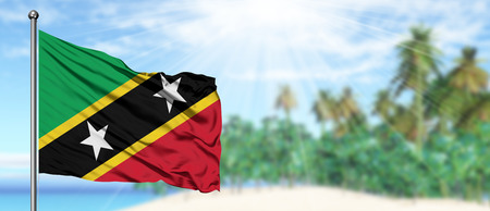 Waving Saint Kitts And Nevis flag in the sunny blue sky with summer beach background. Vacation theme, holiday concept.