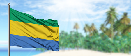 Waving Gabon flag in the sunny blue sky with summer beach background. Vacation theme, holiday concept. Foto de archivo
