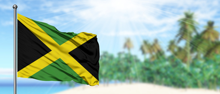 Waving Jamaica flag in the sunny blue sky with summer beach background. Vacation theme, holiday concept. Stock Photo