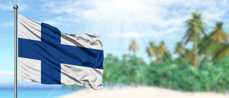 Waving Finland flag in the sunny blue sky with summer beach background. Vacation theme, holiday concept. Stockfoto