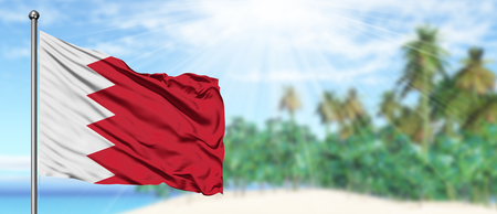 Waving Bahrain flag in the sunny blue sky with summer beach background. Vacation theme, holiday concept. Фото со стока