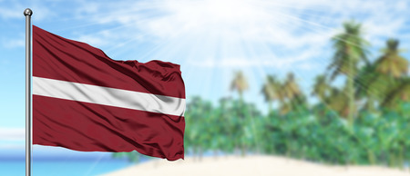 Waving Latvia flag in the sunny blue sky with summer beach background. Vacation theme, holiday concept.