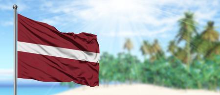 Wehende Lettland-Flagge im sonnigen blauen Himmel mit Sommerstrandhintergrund. Urlaubsthema, Urlaubskonzept. Standard-Bild