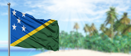 Waving Solomon Islands flag in the sunny blue sky with summer beach background. Vacation theme, holiday concept.