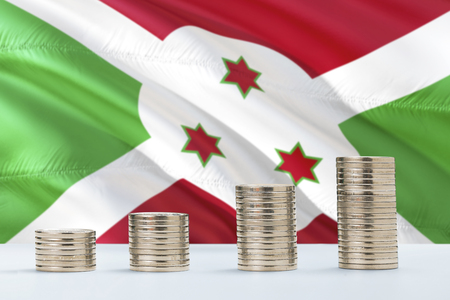 Burundi flag waving in the background with rows of coins for finance and business concept. Saving money. Фото со стока