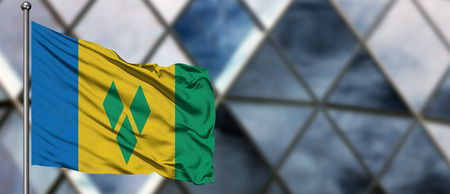 Saint Vincent And The Grenadines flag waving in the wind against blurred modern building. Business concept. National cooperation theme.