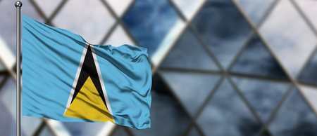 Saint Lucia flag waving in the wind against blurred modern building. Business concept. National cooperation theme. Stock Photo