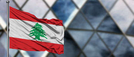 Lebanon flag waving in the wind against blurred modern building. Business concept. National cooperation theme.