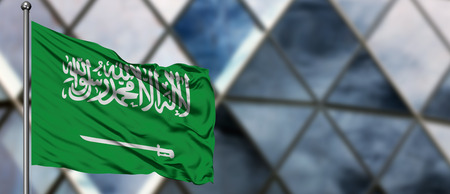 Saudi Arabia flag waving in the wind against blurred modern building. Business concept. National cooperation theme.