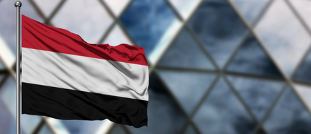 Yemen flag waving in the wind against blurred modern building. Business concept. National cooperation theme.