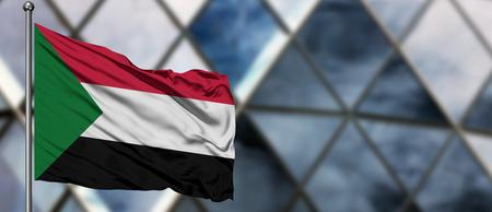 Soedan vlag zwaaien in de wind tegen wazig modern gebouw. Bedrijfsconcept. Nationaal samenwerkingsthema.