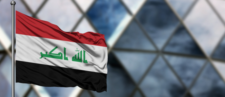 Iraq flag waving in the wind against blurred modern building. Business concept. National cooperation theme. Standard-Bild