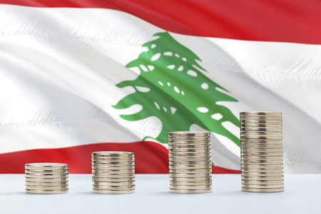 Lebanon flag waving in the background with rows of coins for finance and business concept. Saving money.