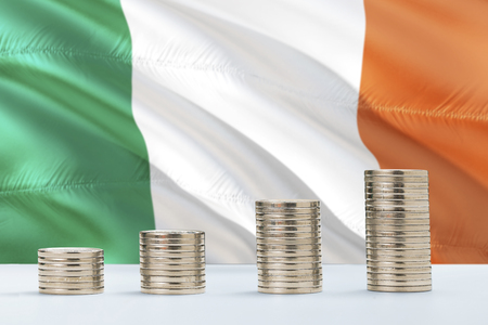 Ireland flag waving in the background with rows of coins for finance and business concept. Saving money. Stock Photo