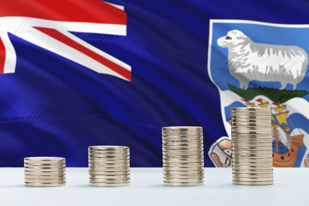 Falkland Islands flag waving in the background with rows of coins for finance and business concept. Saving money.