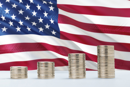 United States flag waving in the background with rows of coins for finance and business concept. Saving money. Фото со стока