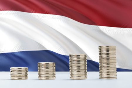 Netherlands flag waving in the background with rows of coins for finance and business concept. Saving money.