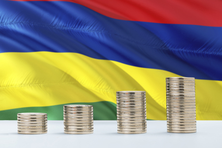 Mauritius flag waving in the background with rows of coins for finance and business concept. Saving money.