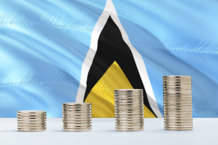 Saint Lucia flag waving in the background with rows of coins for finance and business concept. Saving money.