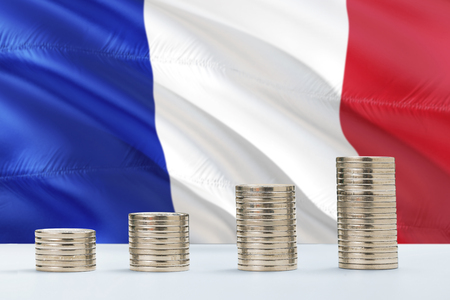 France flag waving in the background with rows of coins for finance and business concept. Saving money.