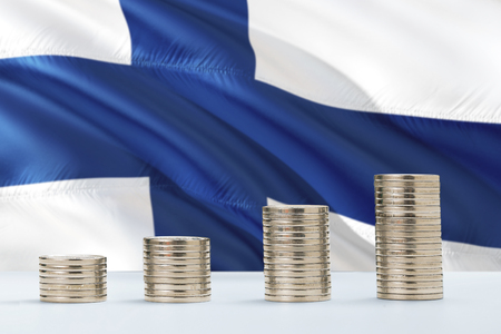 Finland flag waving in the background with rows of coins for finance and business concept. Saving money. Фото со стока