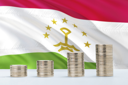 Tajikistan flag waving in the background with rows of coins for finance and business concept. Saving money. Foto de archivo