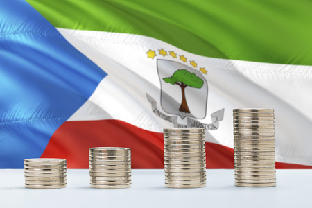 Equatorial Guinea flag waving in the background with rows of coins for finance and business concept. Saving money.