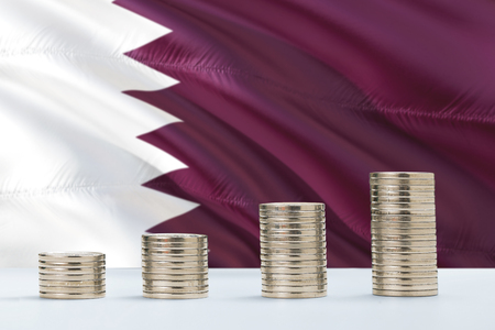 Qatar flag waving in the background with rows of coins for finance and business concept. Saving money. Reklamní fotografie