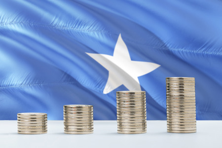 Somalia flag waving in the background with rows of coins for finance and business concept. Saving money. Foto de archivo
