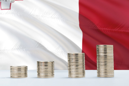 Malta flag waving in the background with rows of coins for finance and business concept. Saving money.