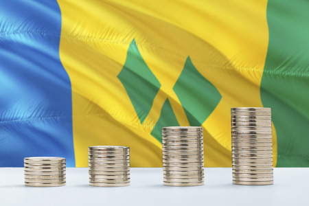 Saint Vincent And The Grenadines flag waving in the background with rows of coins for finance and business concept. Saving money. Фото со стока