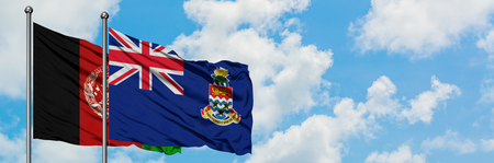 Afghanistan and Cayman Islands flag waving in the wind against white cloudy blue sky together. Diplomacy concept, international relations.