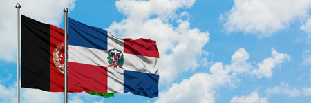 Afghanistan and Dominican Republic flag waving in the wind against white cloudy blue sky together. Diplomacy concept, international relations.