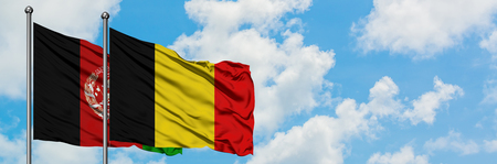 Afghanistan and Belgium flag waving in the wind against white cloudy blue sky together. Diplomacy concept, international relations. Banco de Imagens