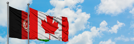 Afghanistan and Canada flag waving in the wind against white cloudy blue sky together. Diplomacy concept, international relations.