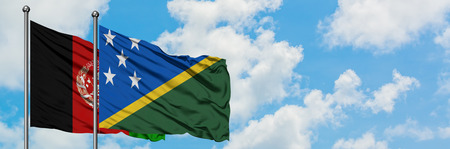 Afghanistan and Solomon Islands flag waving in the wind against white cloudy blue sky together. Diplomacy concept, international relations.