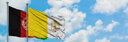 Afghanistan and Vatican City flag waving in the wind against white cloudy blue sky together. Diplomacy concept, international relations.