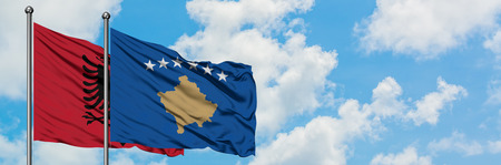 Albania and Kosovo flag waving in the wind against white cloudy blue sky together. Diplomacy concept, international relations.