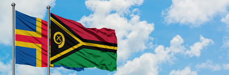 Aland Islands and Vanuatu flag waving in the wind against white cloudy blue sky together. Diplomacy concept, international relations.