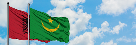Albania and Mauritania flag waving in the wind against white cloudy blue sky together. Diplomacy concept, international relations.