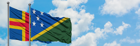 Aland Islands and Solomon Islands flag waving in the wind against white cloudy blue sky together. Diplomacy concept, international relations. Stok Fotoğraf